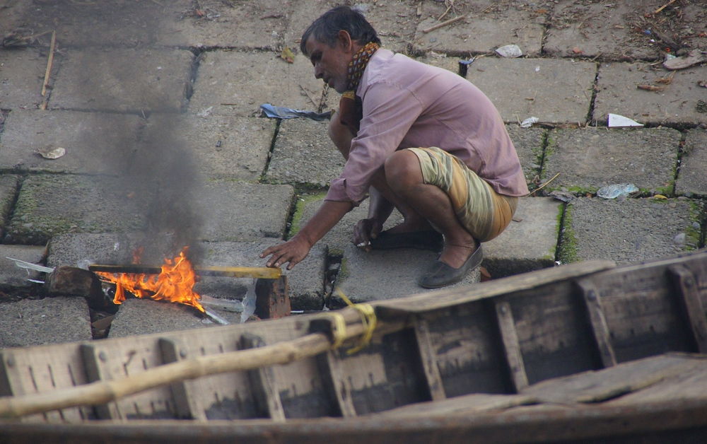 This Bangladeshi man tends to the small fire at the ghat.