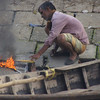 """This Bangladeshi man tends to the small fire at the ghat:<br /> <a href=""""http://nomadicsamuel.com/photo-essays/boat-buriganga-sadarghat-dhaka-bangladesh"""">http://nomadicsamuel.com/photo-essays/boat-buriganga-sadarghat-dhaka-bangladesh</a>"""