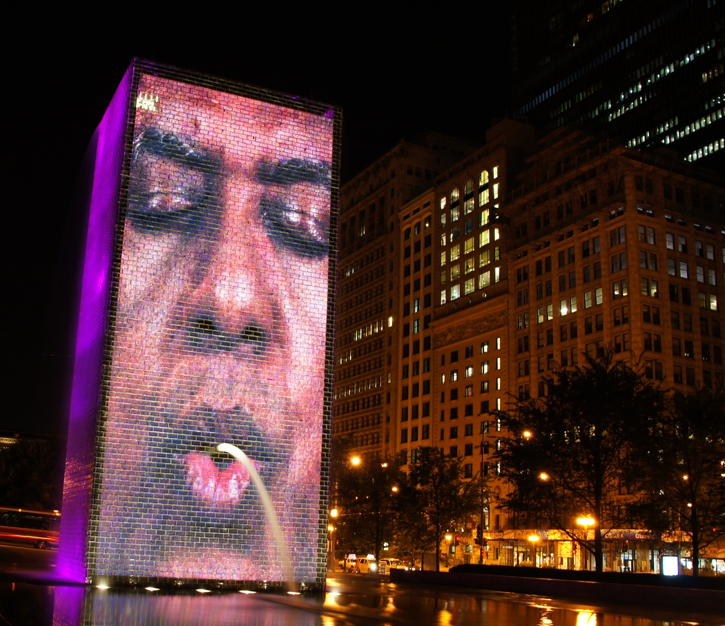 http://nomadicsamuel.com/destinations/chicago-at-night-photo-essay : A man that bares an uncanny resemblance to President Obama spouts out water and flashes neon coloured lights from the Crown Fountain.