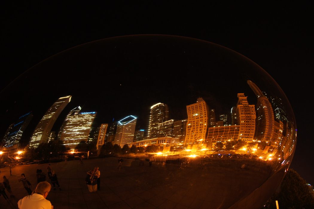 http://nomadicsamuel.com/destinations/chicago-at-night-photo-essay : A couple embraces one another while staring back at their reflection from the Cloud Gate, known by locals as the beam.