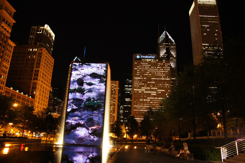 """<a href=""""http://nomadicsamuel.com/destinations/chicago-at-night-photo-essay"""">http://nomadicsamuel.com/destinations/chicago-at-night-photo-essay</a> : A group of scattered individuals sit alongside a long bench taking in the impressive displays coming from the Crown Fountain."""