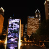 "<a href=""http://nomadicsamuel.com/destinations/chicago-at-night-photo-essay"">http://nomadicsamuel.com/destinations/chicago-at-night-photo-essay</a> : A group of scattered individuals sit alongside a long bench taking in the impressive displays coming from the Crown Fountain."