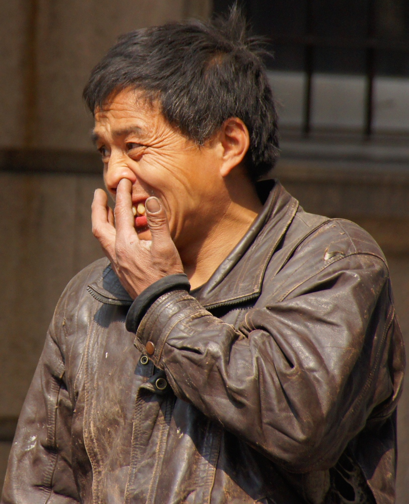 A Chinese man picks his nose on the streets of Shanghai, China.