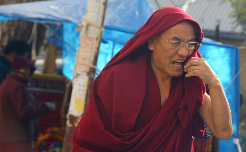 A monk mimicking as though he was using a cell phone - Mcleod Ganj, India.