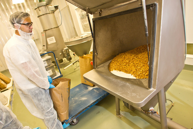 Large quantities of sugar, nonfat milk powder, and dry roasted peanuts are added into the hoppers, along with other ingredients.