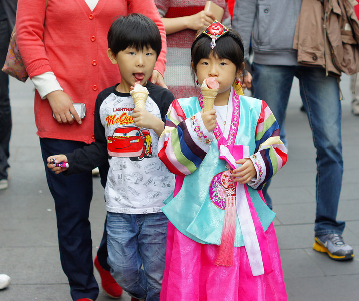 A small Korean boy and girl dressed in traditional attire enjoy a refreshing bite of an ice cream cone.
