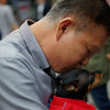 This Korean man shares a cute moment with his dog - dressed in a warm suit - as he tenderly kisses the top of its head.