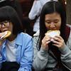 Two Korean girls enjoy hotteok 호떡(Korean style pancake filled with brown sugar, peanuts, cinnamon & honey) in Insadong, Korea.