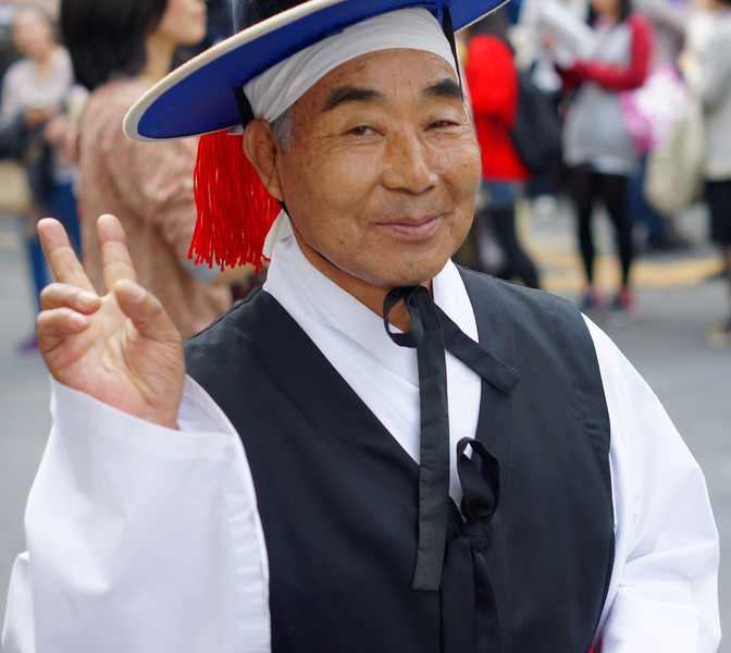 "A Korean man dressed in traditional performing attire makes a peace or 'V"" sign while strolling down Insadong street in Seoul, South Korea."