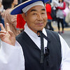 """A Korean man dressed in traditional performing attire makes a peace or 'V"""" sign while strolling down Insadong street in Seoul, South Korea."""