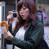 A lady takes a photo of the street food she has just bought by extending her left arm and holding her point and shoot in the other.