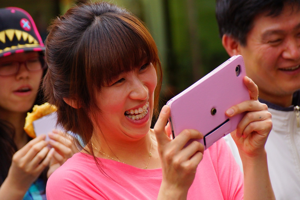 A Korean lady flashes an enormous smiling face while enjoying snapping a photo with her large pink tablet. I still find it a bit strange when seeing people taking photos with these kind of tablets - Insadong, Seoul, Korea.