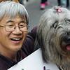 A Korean man wearing glasses and a big grin hugs his dog in Insadong, Seoul, South Korea.