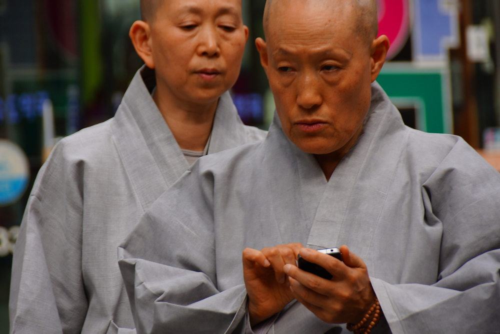 A Korean monk wearing a grey robe texts into messages using his cellphone. I'm at surprised at how many monks I can see in Insadong.