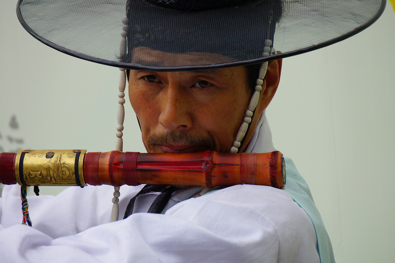 A Korean man wearing traditional attire plays a traditional instrument delighting passing pedestrians.