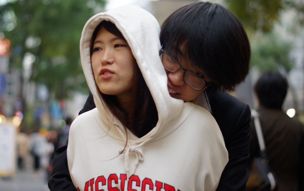 A Korean couple embrace with a hug on the street of Insadong - Seoul, South Korea