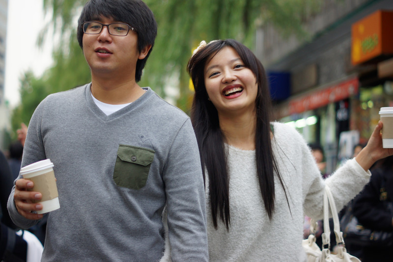 A lovely smiling Korean couple wander down Insadong with coffees in hand - Seoul, South Korea.