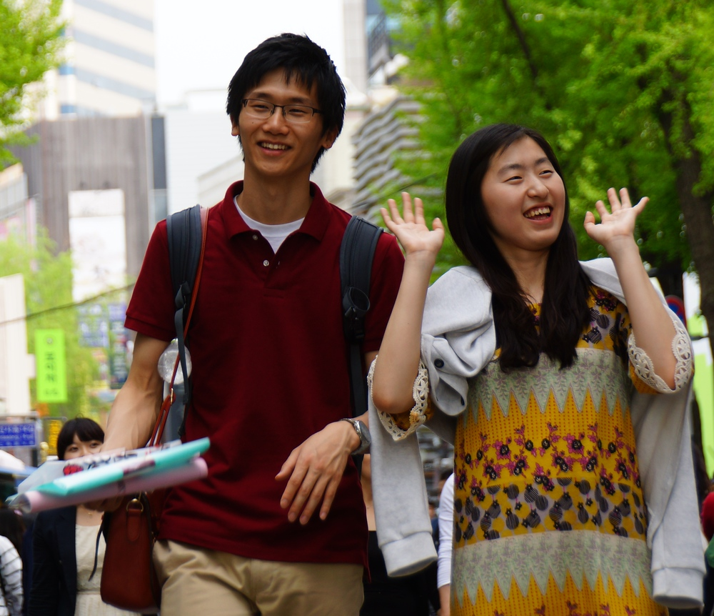 An animated Korean couple share a candid moment on the streets of Seoul, Korea.