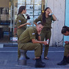 A group of young Israeli soldiers relax in the shade and enjoy refreshments nearby the Flea Market in Jaffa, Israel.