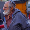 An elderly man with a beard and glasses wanders nearby Mahane Yehuda Market in Jerusalem, Israel.