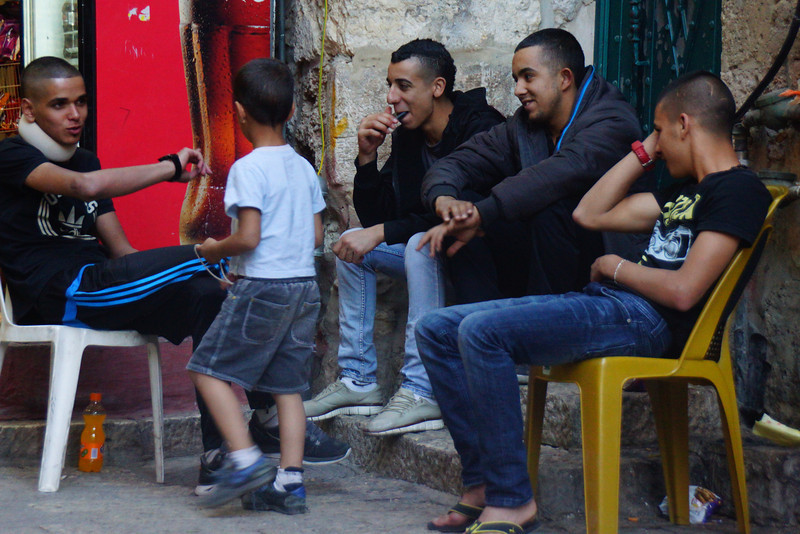 A young child and a group of teenage boys enjoy playing a game and sharing a laugh.