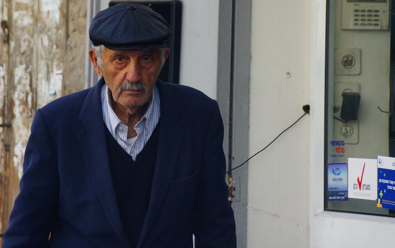 An elderly man wearing a poorboy style hat wanders down the streets of Jerusalem, Israel.