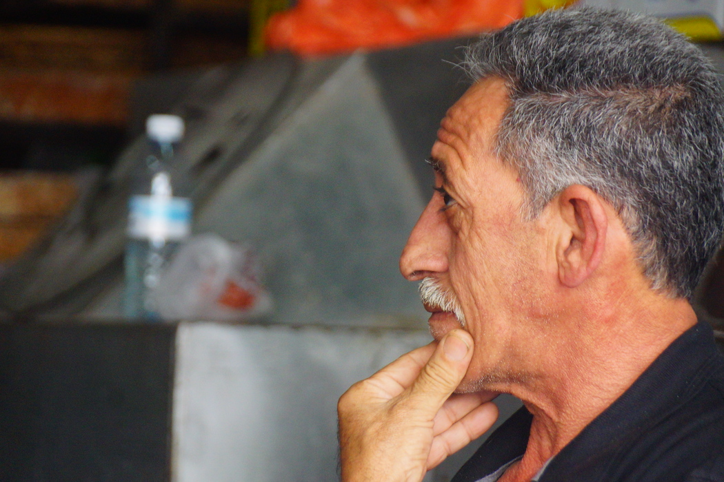 A profile shot of a man who is scratching his chin.
