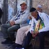 A group of elderly men sit together on a park bench.