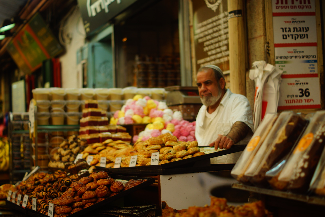 A local baker at Mahane Yehuda Market tends to his pastries that are on display.
