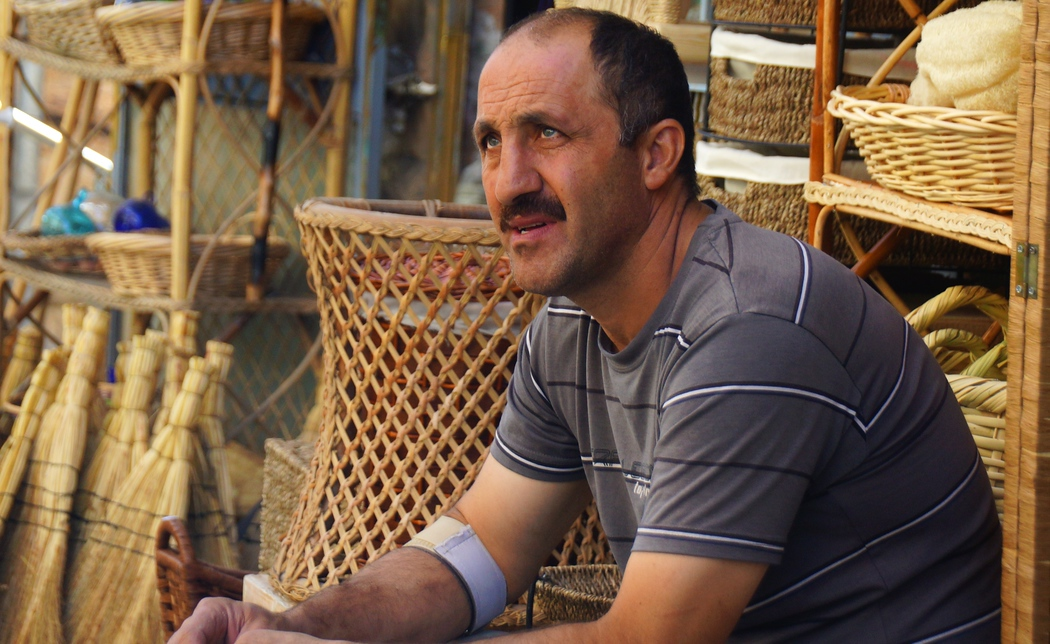 A candid portrait of a man sitting down outside a basket shop.