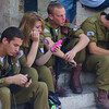A group of young Israeli soldiers sit down and play with their cellphones prior to a special ceremony taking place in Old Jerusalem, Israel.