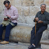 An elderly man with a distinct face and cane sits down in the shade in Old Jerusalem, Israel.