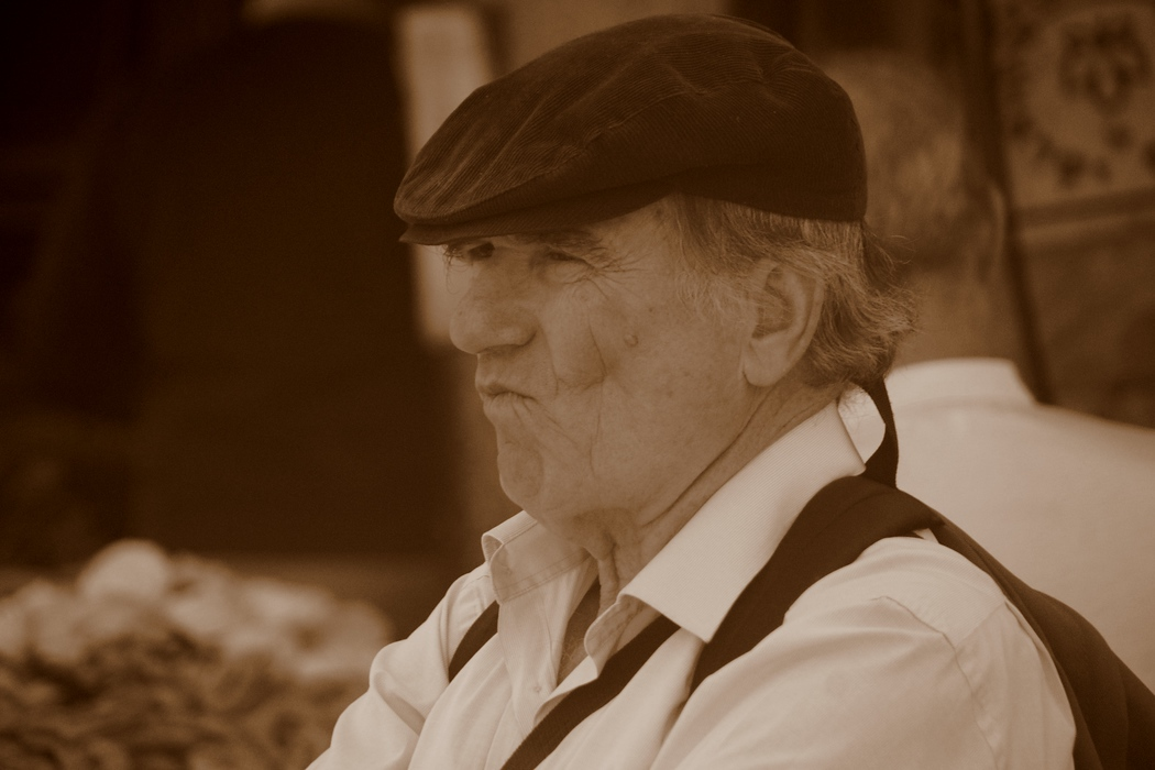 A man wearing a poorboy hat with a distinct face.