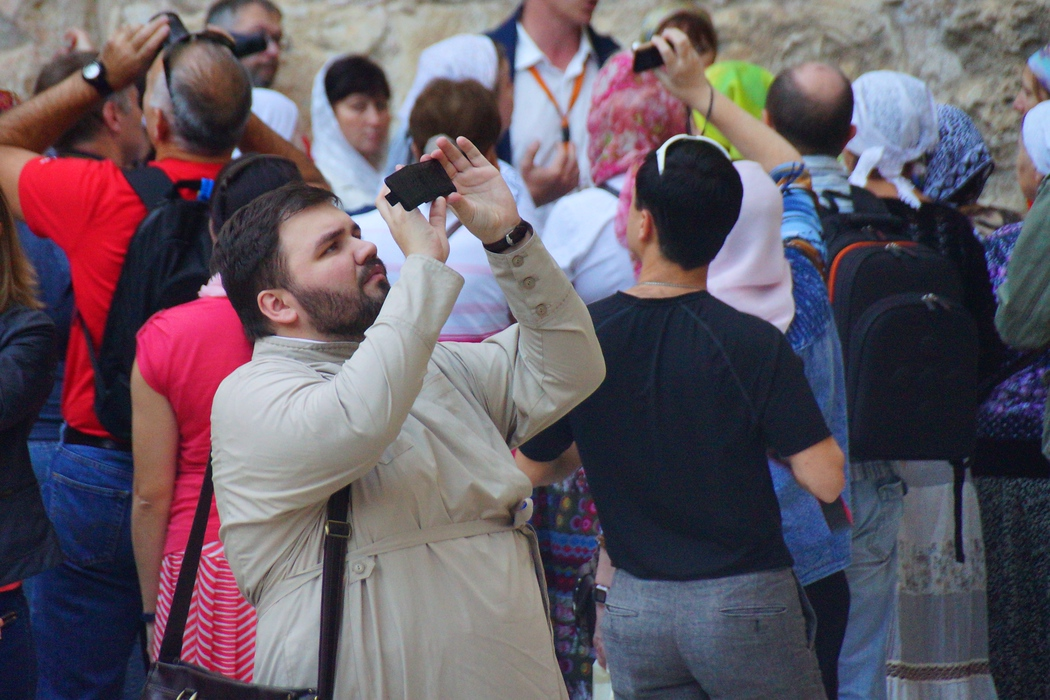 A tourists snaps a photo cellphone camera in one of the busiest areas of Old Jerusalem, Israel.