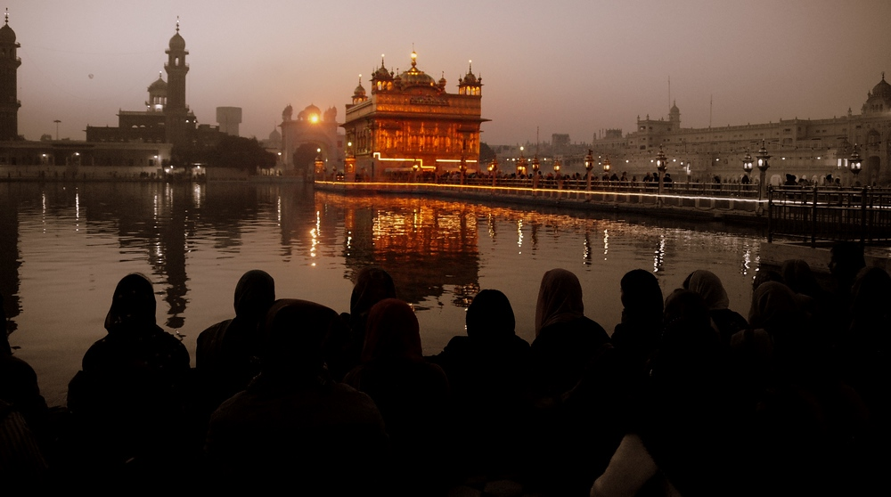 This group of people marvel at the Harmandir Sahib from a distance.
