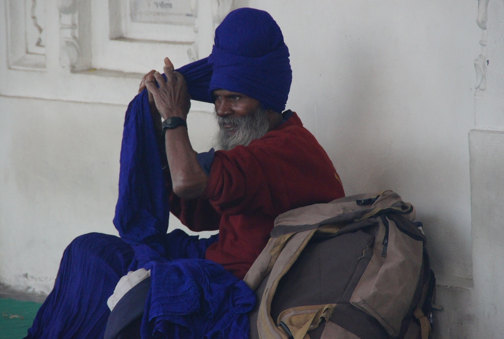 This man takes great care in wrapping the blue headdress around his head.
