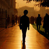A silhouette shot of a man walking around during sunset.