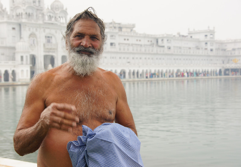 A photo of bare chested man with distinct smile and an impressive beard.