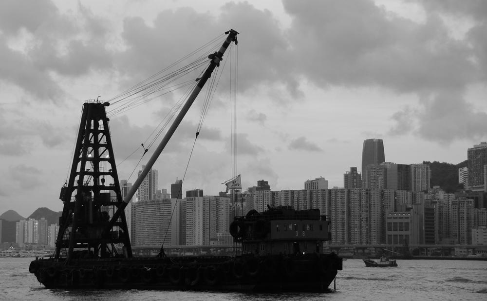 A large shipping vessel makes its way through the Hong Kong - Kowloon divide.