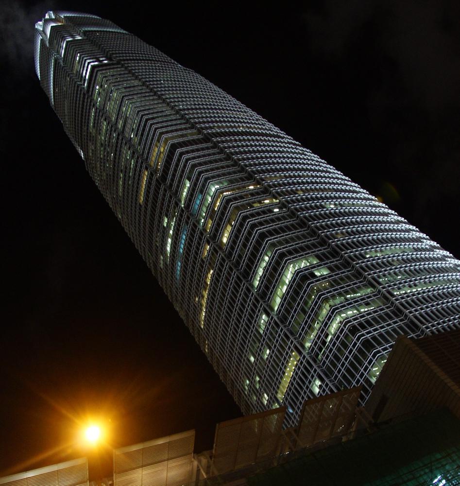 Two international finance centre building stands tall and illuminated at night - Hong Kong Island, China.
