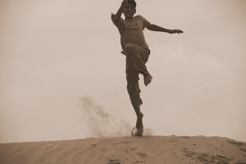 This is a travel photo of a man of a man/boy jumping off a sand dune in the Thar Desert, India