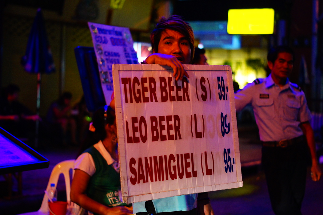 http://nomadicsamuel.com : A Thai vendor tries to encourage passing crowds to stop at his makeshift curbside bar for a beer.