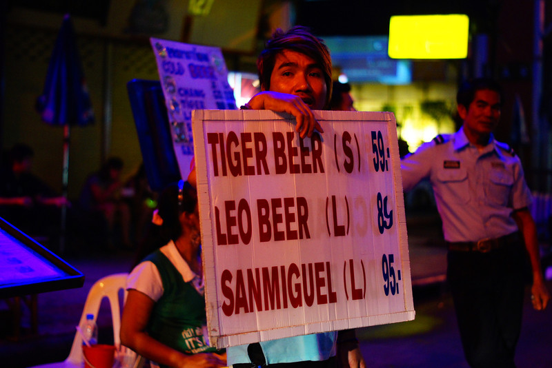 """<a href=""""http://nomadicsamuel.com"""">http://nomadicsamuel.com</a> : A Thai vendor tries to encourage passing crowds to stop at his makeshift curbside bar for a beer."""