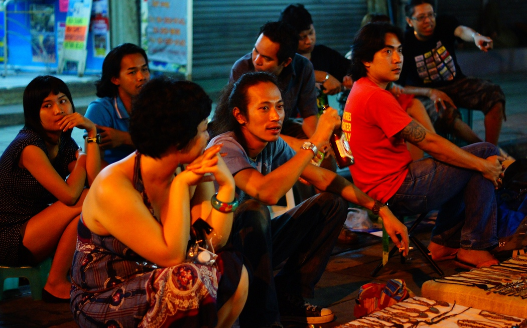 http://nomadicsamuel.com : A Thai crowd hovers outside this section of the street curb selling all kinds of different trinkets and drinking beer.