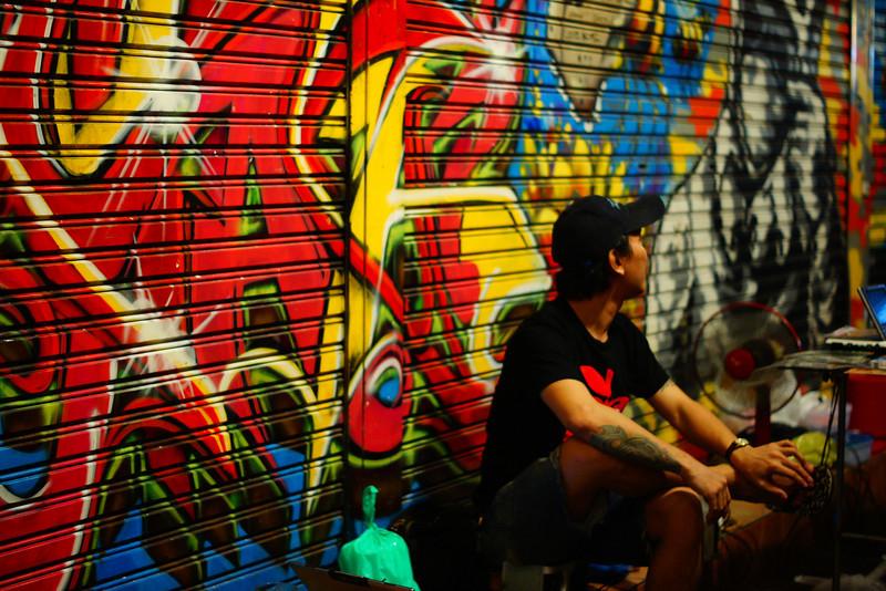 "<a href=""http://nomadicsamuel.com"">http://nomadicsamuel.com</a> : A man sits down beside a fan to cool off alongside a graffiti ridden wall in a side alley just off of Khao San Road - Bangkok, Thailand."