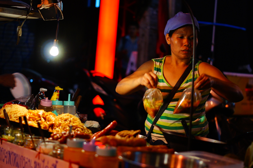 http://nomadicsamuel.com : A Thai lady vendor prepares packages of curry and soup.