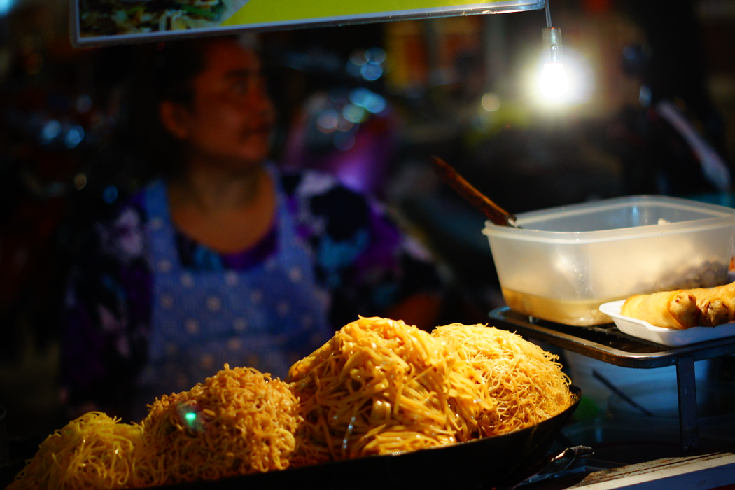 https://nomadicsamuel.com : This shot shows the ingredients of Phad Thai with the vendor who is preparing it blurred in the background.