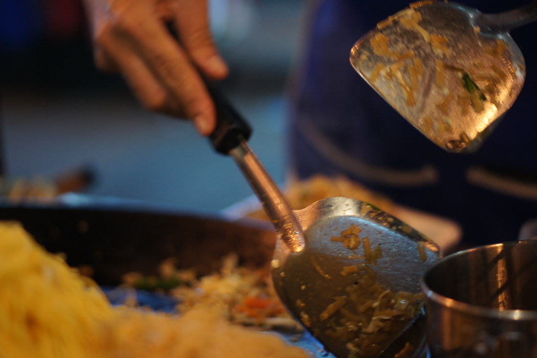 http://nomadicsamuel.com : The scraping of utensils as a man fries Pad Thai.