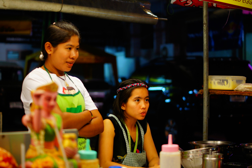 https://nomadicsamuel.com : A Thai lady looks on at potential customers nearby a parking lot.