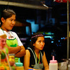 "<a href=""http://nomadicsamuel.com"">http://nomadicsamuel.com</a> : A Thai lady looks on at potential customers nearby a parking lot."